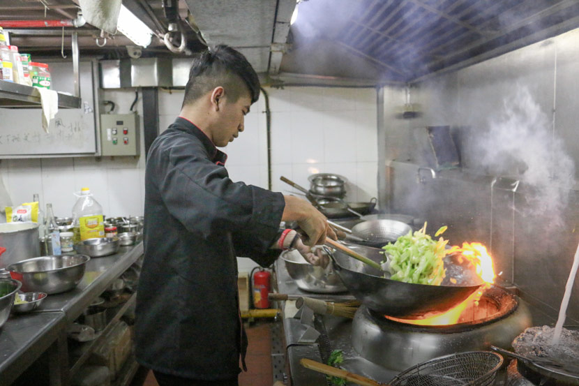 Deng Xin cooks at a restaurant in Shantou, Guangdong province, May 26, 2018. Cai Yiwen/Sixth Tone