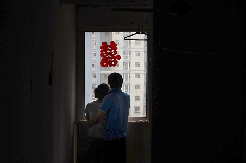 Newlyweds stand by the window at their home in Tianjin, July 26, 2011. Xiao Chunhu/VCG