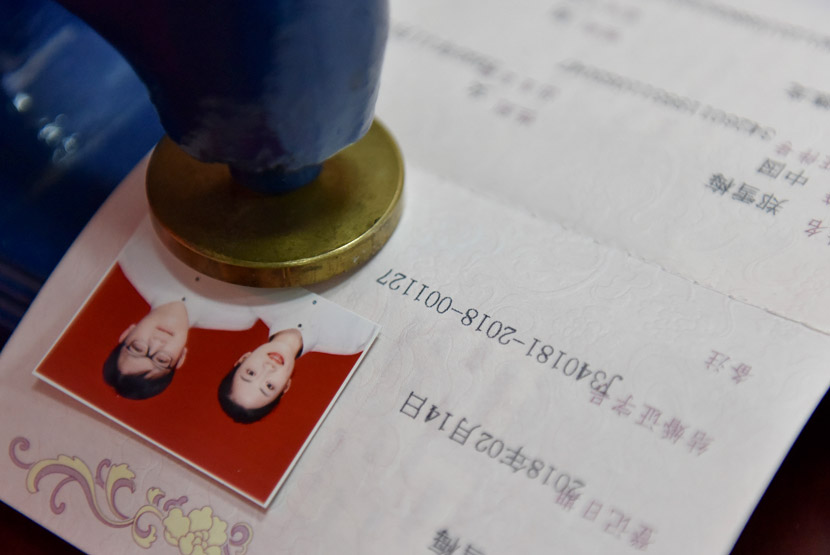 An official stamps a marriage certificate at a civil affairs bureau in Chaohu, Anhui province, Feb. 14, 2018. Ma Fengcheng/VCG