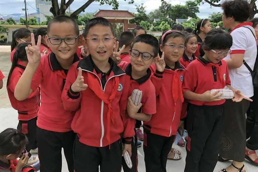 Students pose for a photo after receiving new glasses in Longchuan County, Yunnan province, June 6, 2018. From the Weibo account of Education in Sight