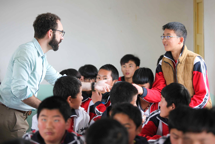 Andrew Shirman shakes hands with a student at a school in Yunnan province. From the website of Mantra