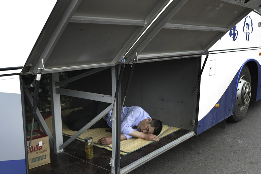 A driver takes a nap inside the luggage compartment of a bus in Nanjing, Jiangsu province, June 6, 2007. Xiao En/VCG