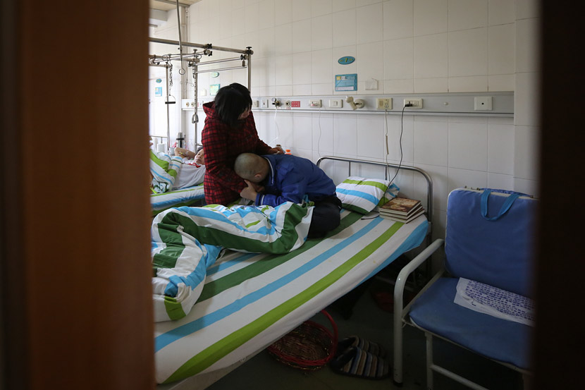 A teenager suffering from bone cancer hugs his mother at a hospital in Xiaogan, Hubei province, April 9, 2015. Ma Luyao/VCG
