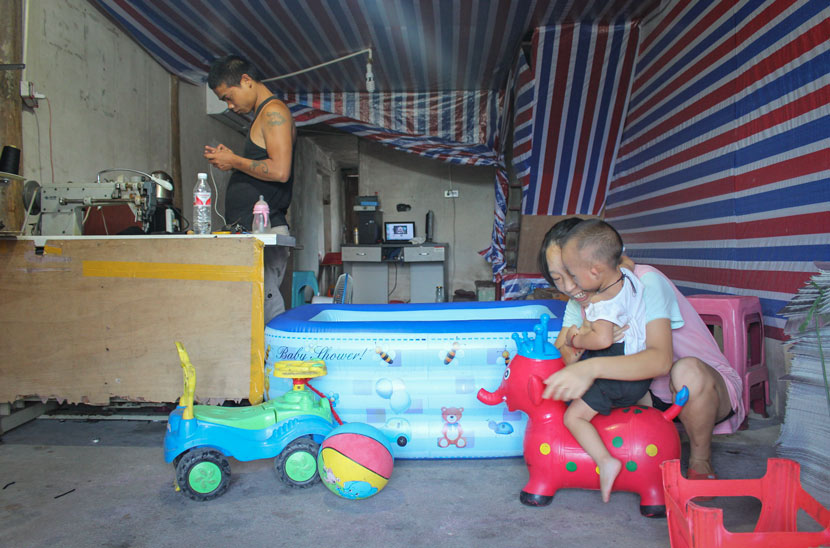 Zhang Yueying plays with her son while her husband stands by a sewing machine at their home in Shi'erdai Village, Zhejiang province, Aug. 4, 2018. Xue Yujie/Sixth Tone