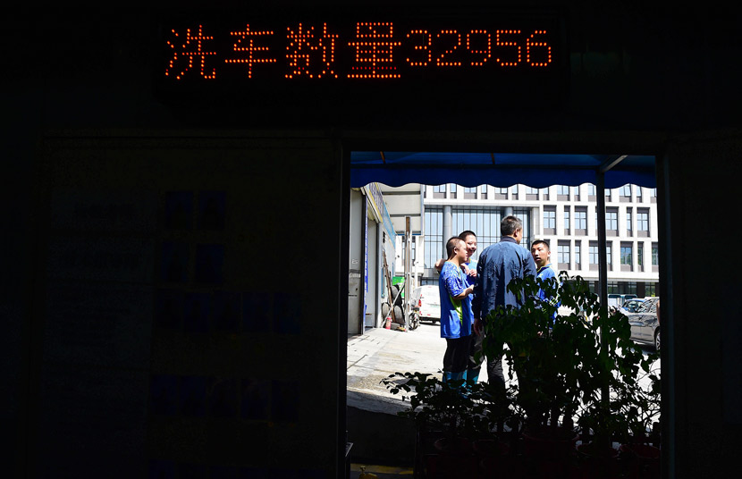 Cao Jun (middle) talks to Xihaner Car Wash employees as a screen counts the number of cars washed, Shenzhen, Guangdong province, April 25, 2018. Liao Jian/VCG