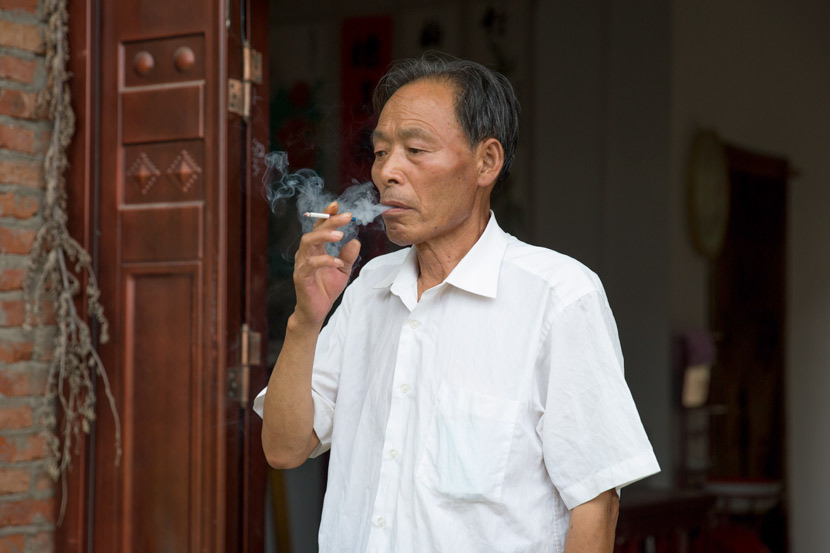 Yan Hongchang smokes outside his home in Xiaogang, Anhui province, July 25, 2018. Shi Yangkun/Sixth Tone