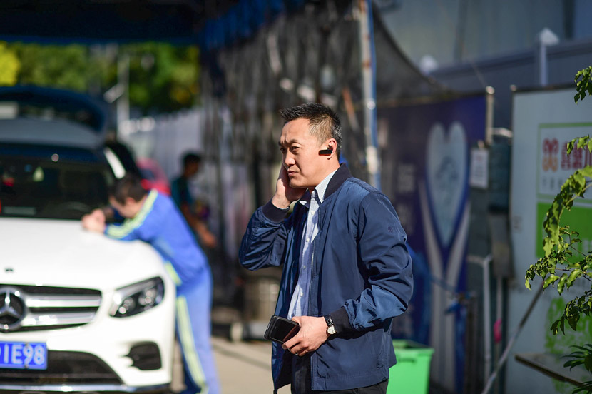 Cao Jun takes a phone call at Xihaner Car Wash in Shenzhen, Guangdong province, April 25, 2018. Liao Jian/VCG