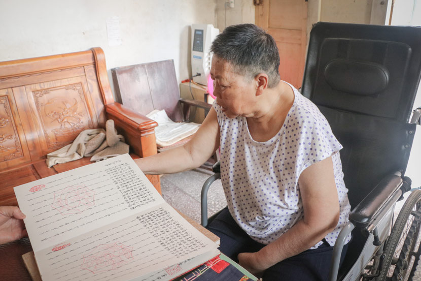 He Jinghua reads from her personal journal written in 'nüshu' at her home in downtown Jiangyong County, Hunan province, July 19, 2018. Yin Yijun/Sixth Tone