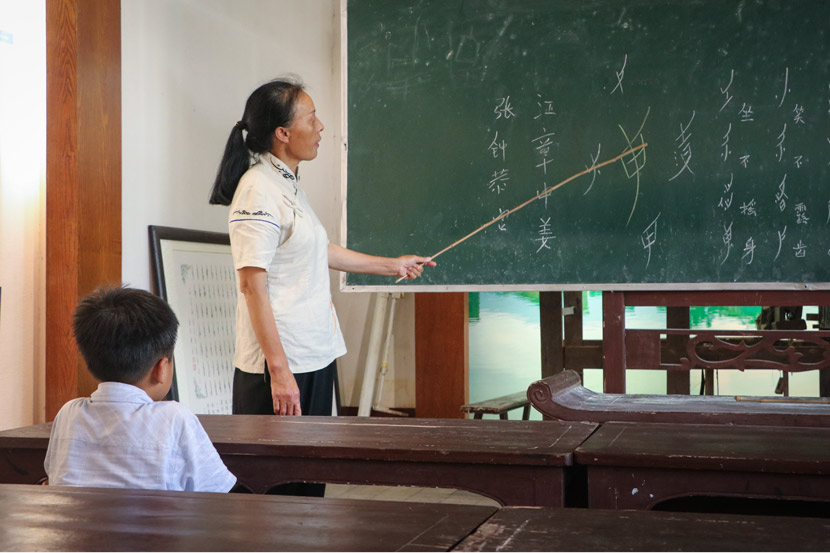 Hu Meiyue, 'nüshu' inheritor and guide, teaches visitors at Nüshu Museum in Jiangyong County, Hunan province, July 18, 2018. Yin Yijun/Sixth Tone