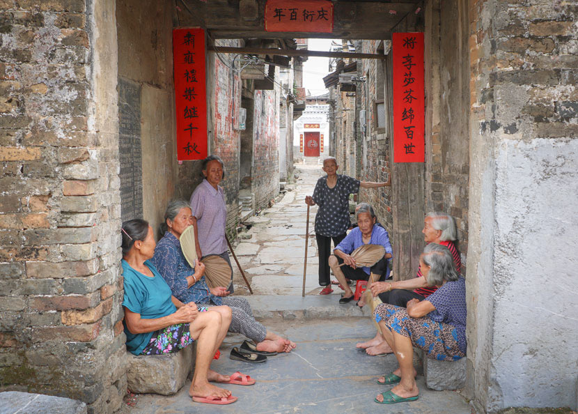 He Yanxin spends her leisure time chatting with elders in the alleyways of Heyuan Village, in Jiangyong County, Hunan province, July 18, 2018. Yin Yijun/Sixth Tone