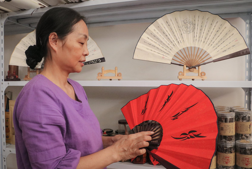 Pu Lijuan, He Jinghua's daughter, displays a fan decorated with 'nüshu' script at her home in Jiangyong County, Hunan province, July 19, 2018. Yin Yijun/Sixth Tone
