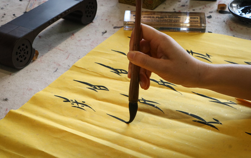 Hu Xin writes 'nüshu' at Nüshu Museum in Jiangyong County, Hunan province, July 18, 2018. Yin Yijun/Sixth Tone
