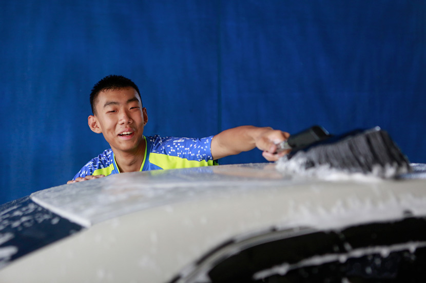 An employee washes a car at Xihaner in Shenzhen, Guangdong province, April 25, 2018. Liao Jian/VCG