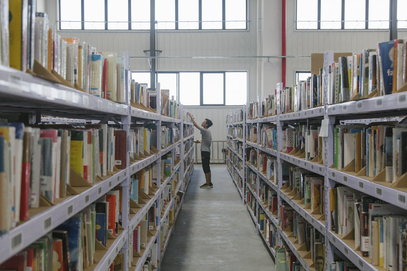A Déjà Vu employee picks books in the company's warehouse in Tianjin, July 31, 2018. Wu Huiyuan/Sixth Tone
