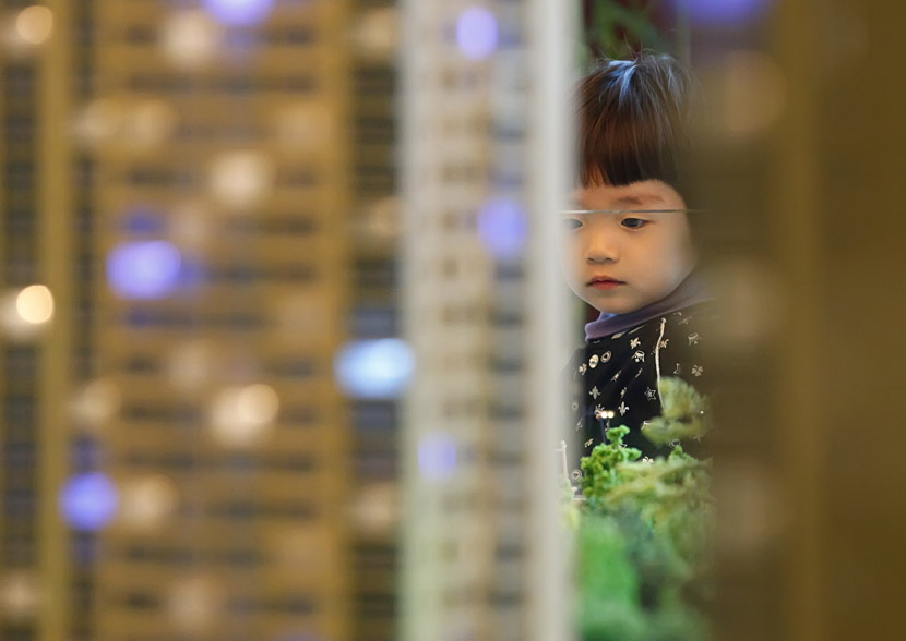 A girl looks at a housing model in a sales office in Changchun, Jilin province, April 23, 2011. Sun Jinglei/VCG