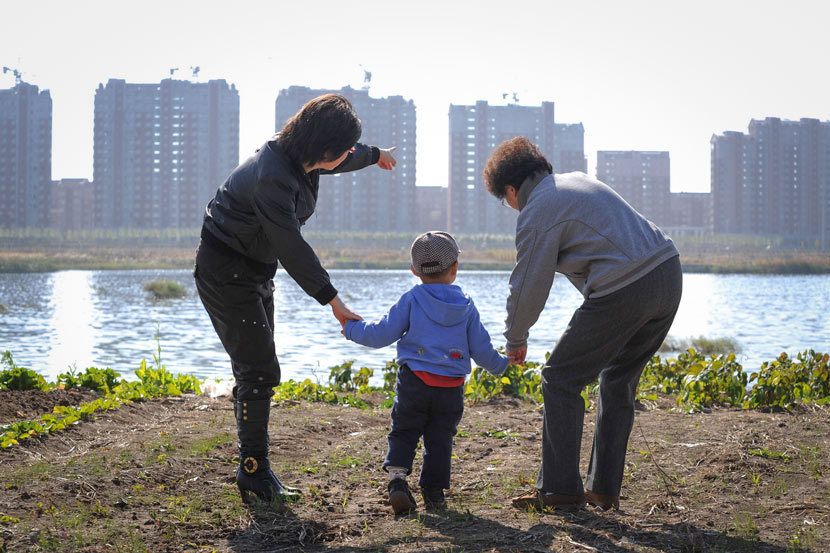A mother points out new apartment buildings while taking her child out for a walk in Changchun, Jilin province, 2010. Zhang Xiyu/IC