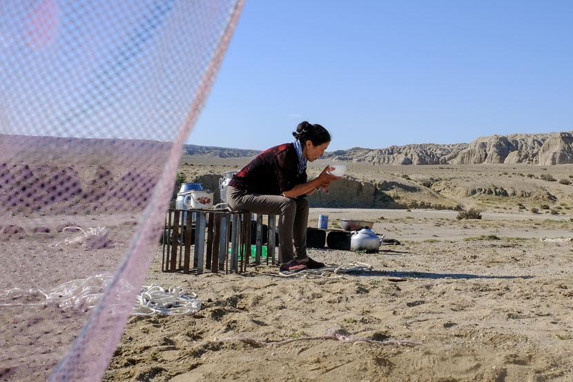 Aykush Kaken's wife, Gana Guli Kahan, rests after her morning chores outside their yurt in Fuhai County, Xinjiang Uyghur Autonomous Region, July 10, 2018. Bibek Bhandari/Sixth Tone