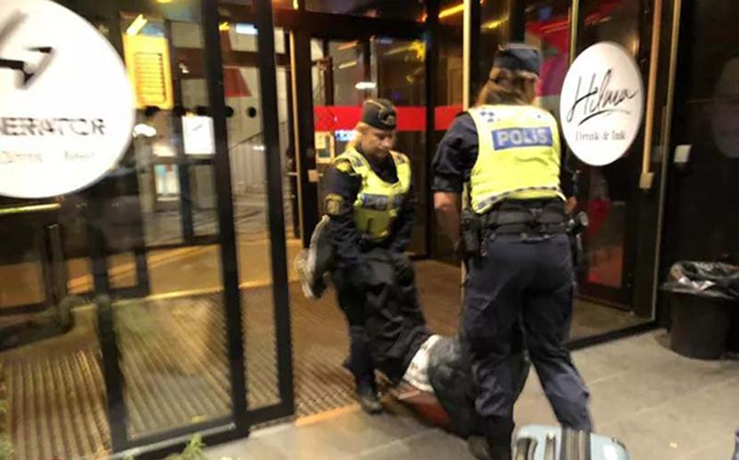 A screenshot from a cellphone video shows Swedish police carrying Zeng's father out of the hostel. From Weibo user @环球时报