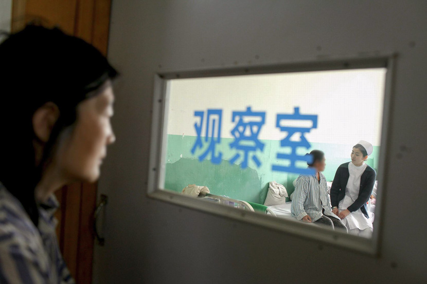 A patient looks on as a nurse talks with another patient at a psychiatric hospital in Anshan, Liaoning province, May 9, 2014. VCG