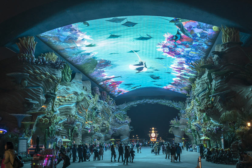 Visitors pass underneath an aquarium tank at the Chimelong Ocean Kingdom theme park in Zhuhai, Guangdong province, Jan. 26, 2018. Wang Gang/VCG