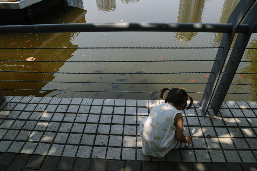 A girl plays by Dongshan Lake in a park in Guangzhou, Guangdong province, Sept. 11, 2018. Li You/Sixth Tone