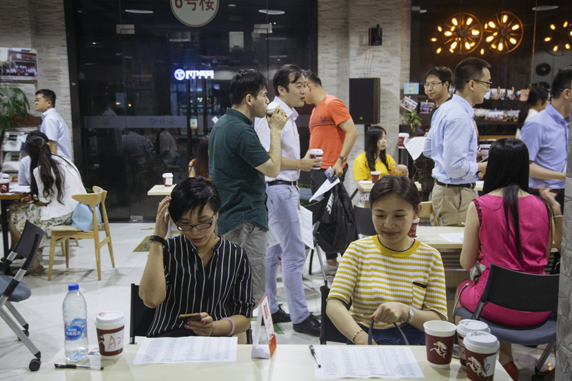 Male attendees move on to the next table after an 8-minute-date during a matchmaking event in Shanghai, July 27, 2018. Wu Huiyuan/Sixth Tone