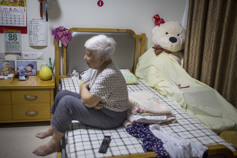 An elderly woman sits on her bed at Sunshine Home in Hangzhou, Zhejiang province, Sept. 28, 2018. The plush teddy bear is a gift from her grandson. Chen Zhongqiu for Sixth Tone
