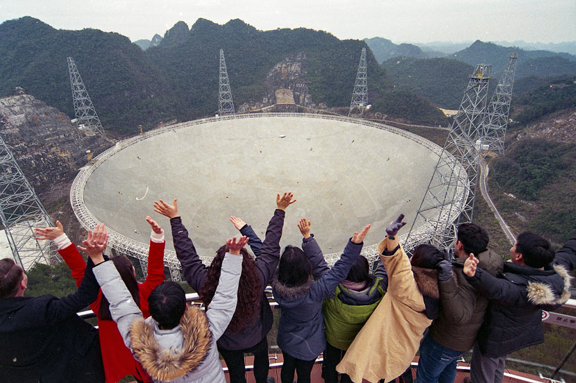 Young people pose for a photo in front of the Five-hundred-meter Aperture Spherical Telescope in Pingtang County, Guizhou province, Jan. 13, 2018. He Junyi/CNS/VCG