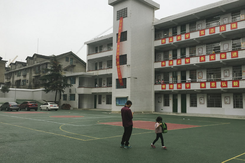 A father and his daughter wait for the girl's older sibling to finish classes at the newly built Xinhua Experimental Middle School in Xinhua County, Hunan province, Sept. 25, 2018. Ni Dandan/Sixth Tone