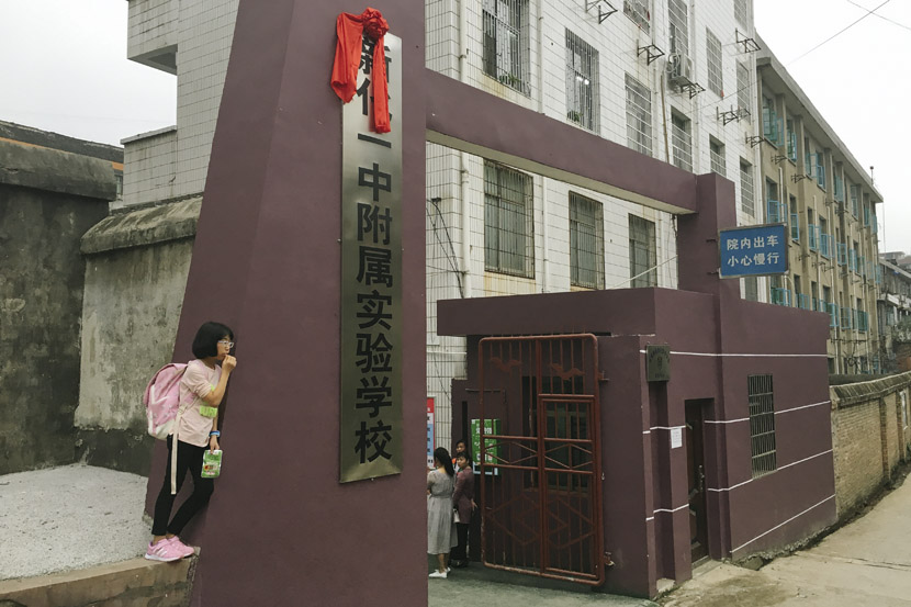 A girl leans against the gate of Xinhua Experimental Middle School, which had just been converted from the local education bureau's offices over the summer break in Xinhua County, Hunan province, Sept. 25, 2018. Ni Dandan/Sixth Tone