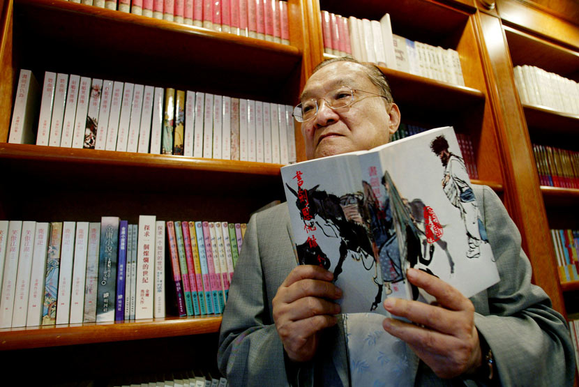 Louis Cha poses for a photo while holding a copy of his novel 'The Book and the Sword' in Hong Kong, July 29, 2002. Bobby Yip/Reuters/VCG