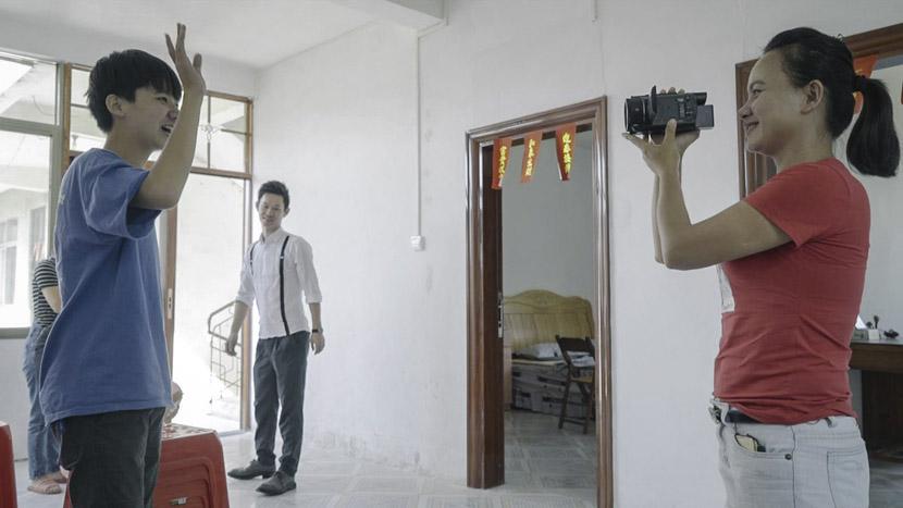Gan Youqin films her son greeting her fans on-camera in a relative's house, Lingshan County, Guangxi Zhuang Autonomous Region, Oct. 1, 2018. Tang Xiaolan/Sixth Tone