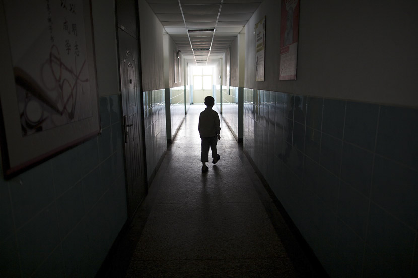 A boy meanders down the hallway of a school in Beijing, May 31, 2012. Zhou Gangfeng/Beijing News/VCG