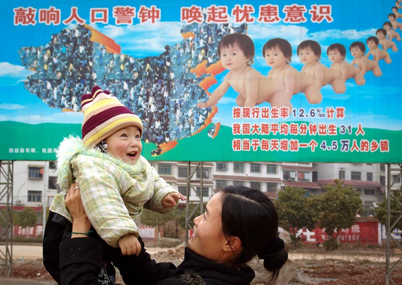 A woman holds up her child in front of a billboard about the one-child policy in Xinshao County, Hunan province, Feb. 1, 2005. IC