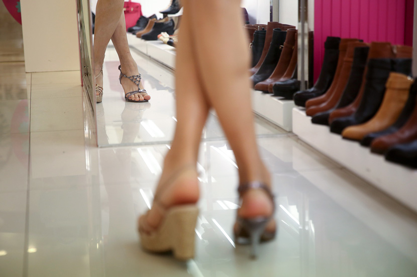 A transgender woman tries on a pair of heels at a shoe store in Guangzhou, Guangdong province, April 6, 2015. VCG