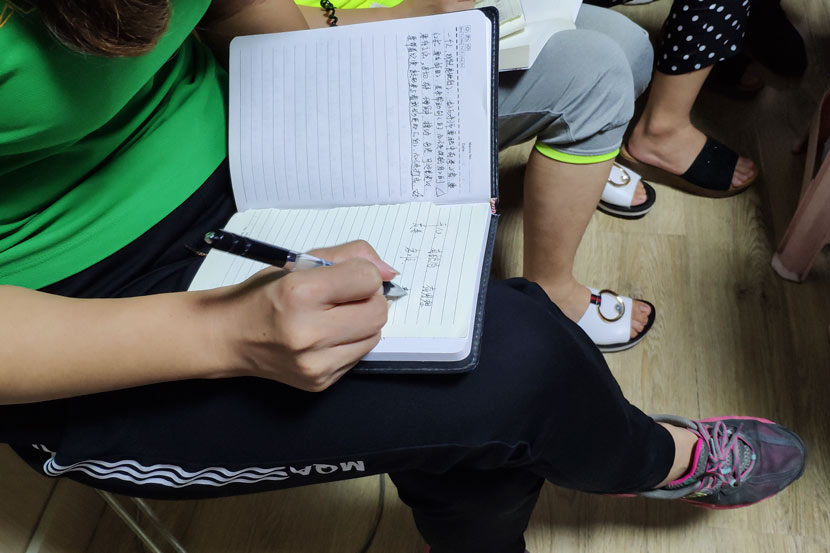 A parent takes notes during a child-rearing class in Zoucheng, Shandong province, Sept. 5, 2018. Fan Yiying/Sixth Tone