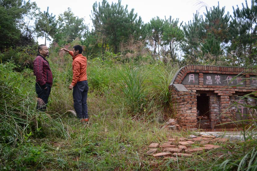 The youngest son of the Xiao family (right) stands near a tomb prepared for his mother a year ago in Hetian Village, Jiangxi province, Oct. 17, 2018. According to local custom, preparing a tomb prior to the death of its intended inhabitant brings good luck to the family. Fan Liya/Sixth Tone