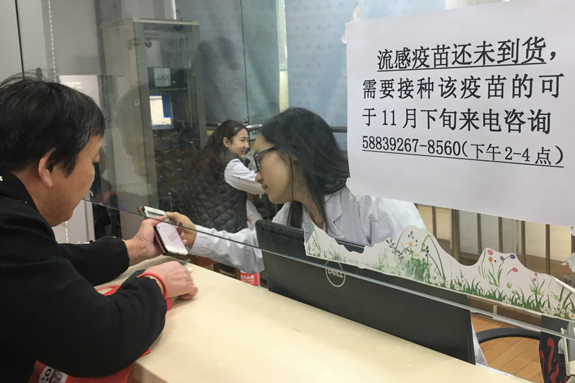 A woman asks a staff member about a flu vaccine at a community health service center in Pudong District, Shanghai, Nov. 9, 2018. Ni Dandan/Sixth Tone