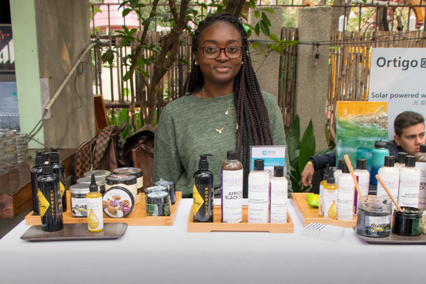 Anita Nuo-Ire Maala poses at her booth for hair and skin care products at Black Expo in Shanghai, Nov. 24, 2018. Kenrick Davis/Sixth Tone