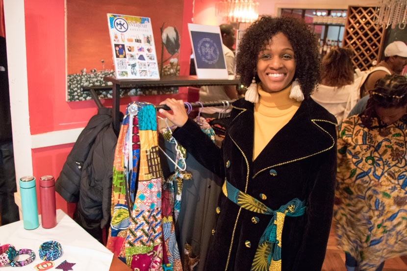 Whitney Omari-White poses next to Ghanaian-made clothes at her Black Expo stall in Shanghai, Nov. 24, 2018. Kenrick Davis/Sixth Tone