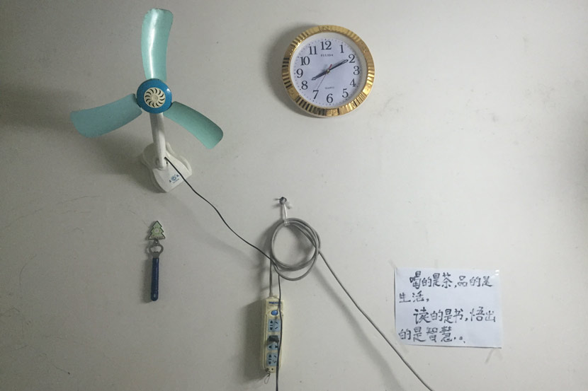A view of the wall of Tan Song'an's dining room in Shenzhen, Guangdong province, Nov. 2, 2018. The small fan helps the family cope with the summer heat, and the note on the wall is from Tan to his son, encouraging him not to dwell on life's troubles. Cai Yiwen/Sixth Tone