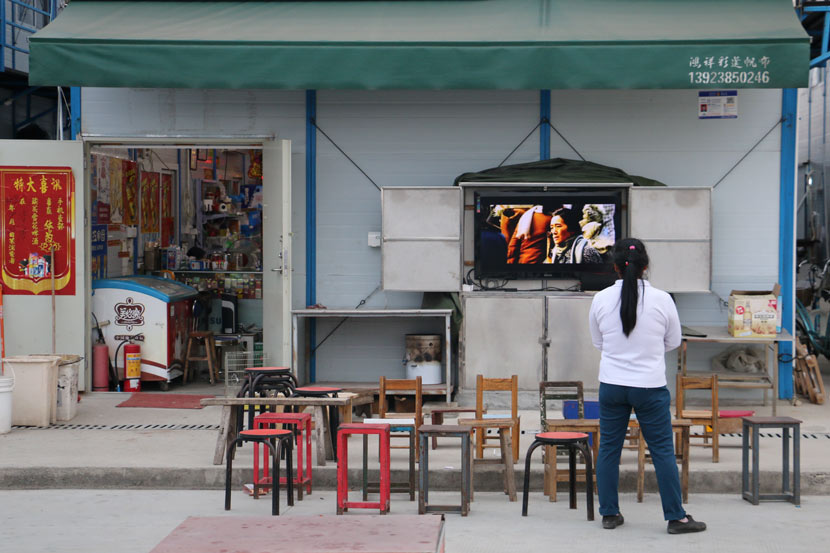 A worker watches television outside a small shop near a construction site, Shenzhen, Guangdong province, Nov. 2, 2018. Cai Yiwen/Sixth Tone