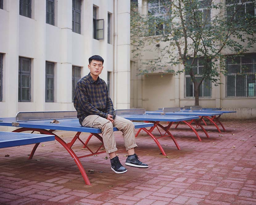 Guo Tianlong, from Nanjie Village, sits on a pingpong table in Henan province, 2018. Shi Yangkun/Sixth Tone