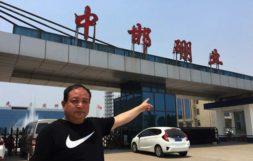 Wang Zengliang points to the gate of his factory in Handan, Hebei province, 2017. From @中国青年报 on Weibo