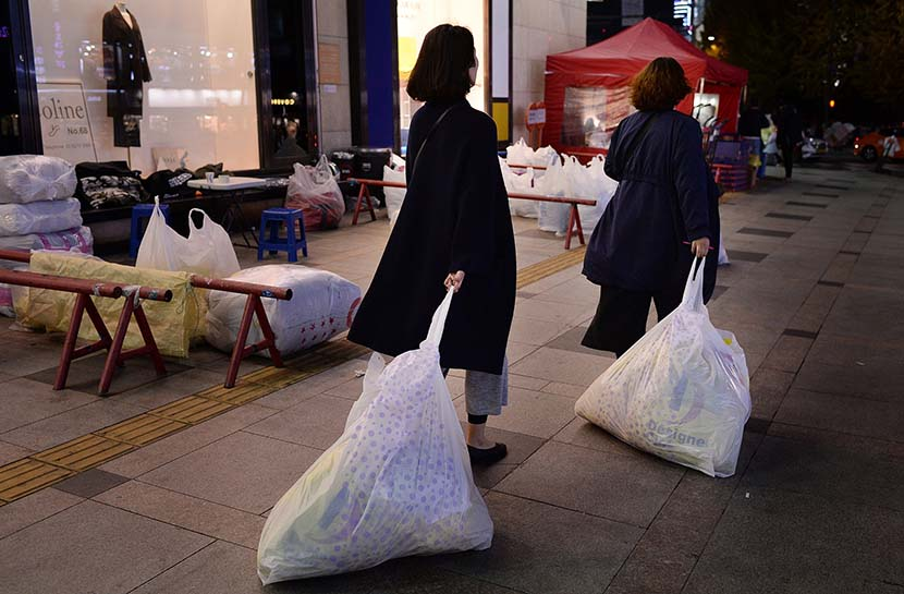 Two Chinese 'daigou' drag bags through Dongdaemun Market in Seoul, South Korea, Nov. 14, 2016. VCG