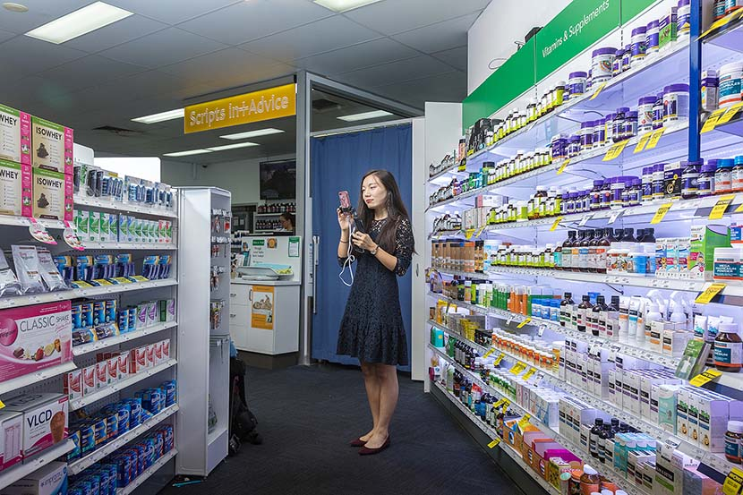 A woman livestreams while purchasing health products for her Chinese customers in Brisbane, Australia, April 18, 2018. VCG
