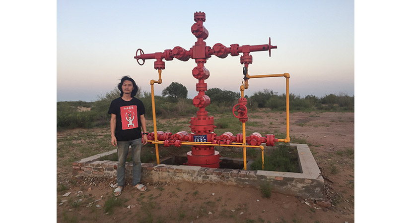 The artist Brother Nut poses for a photo near a gas well in Xiaohaotu Township, Shaanxi province, July 2018. Courtesy of Brother Nut