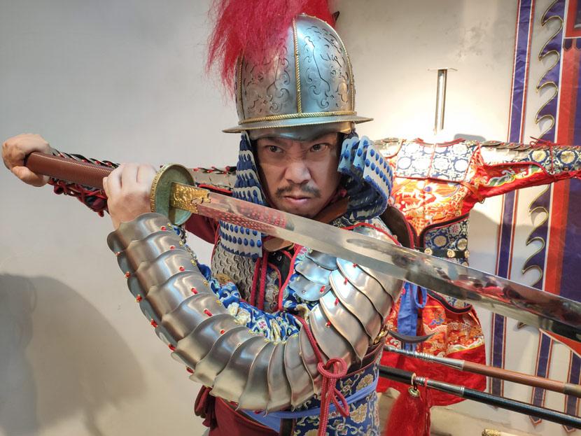 Liu Shiwei strikes a fierce pose at an underground armor store in Shanghai, Dec. 10, 2018. Kenrick Davis/Sixth Tone
