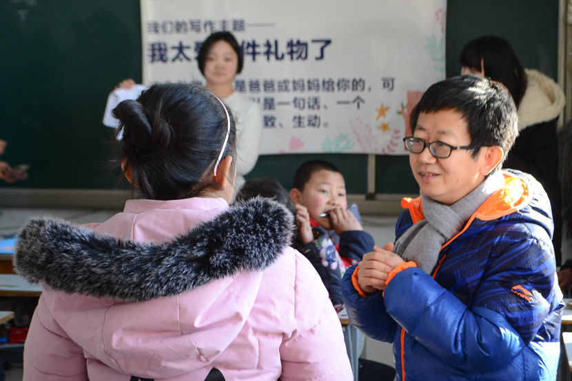 Guan Jun talks to a student during class at Minren Primary School in Beijing, Dec. 13, 2018. Fan Liya/Sixth Tone