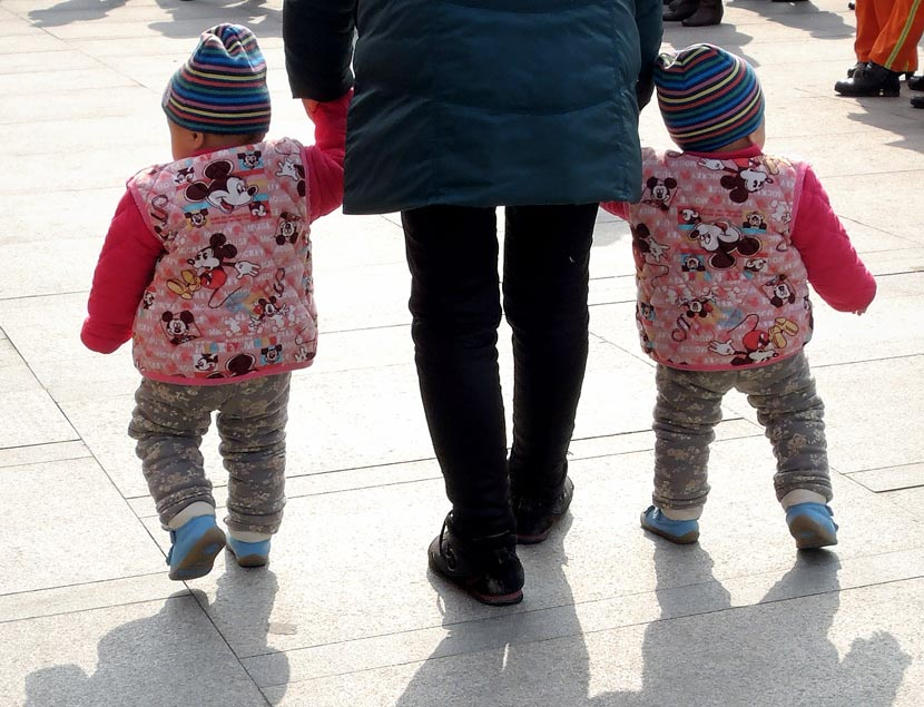 A parent holds hands with their two children in Nanjing, Jiangsu province, March 5, 2014. An Xin/VCG